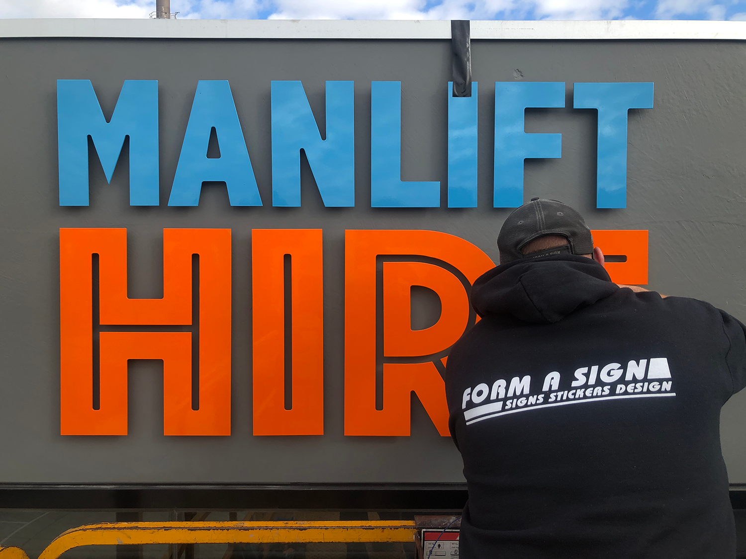 manlift hire external business signage being installed