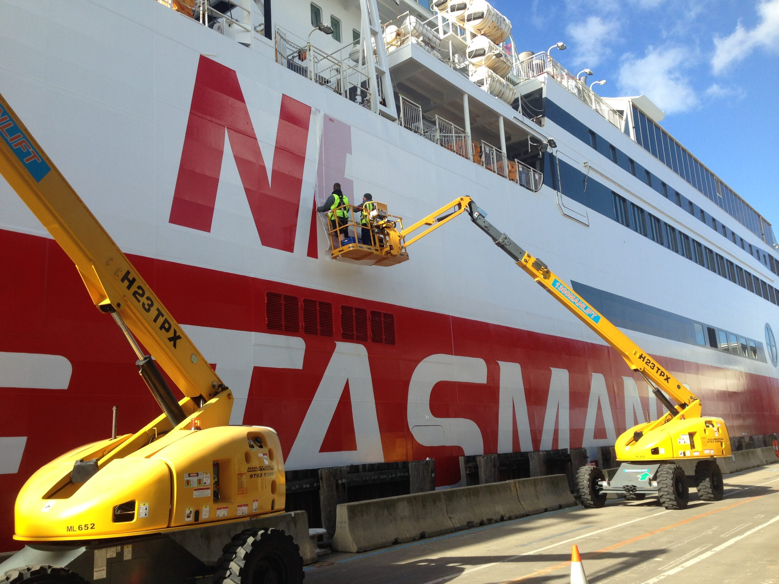installing vinyl signage on the spirit of tasmania in a cherry picker